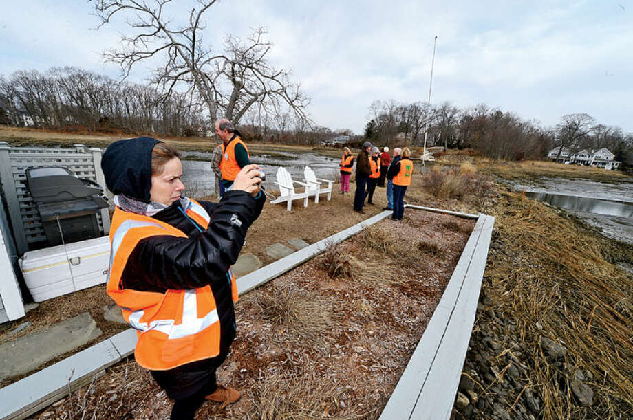 Hour photo / Erik Trautmann Phyllis Padro gets a shot of the salt marsh as the group hikes to view Old Trolly peninsula at 2 Nearwater Lane as the Norwalk Land Trust hosts a tour of all of its properties Saturday morning.