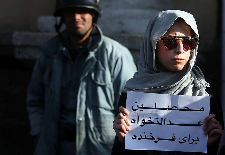 """An Afghan university student protests at the site where a mob beat to death a 27 year-old woman, Farkhunda, in Kabul, Afghanistan, Thursday, March 26, 2015. Farkhunda, who went by one name like many Afghans, was beaten, run over with a car and burned before her body was thrown into the Kabul River, last week. Persian on the poster reads, """"university students, justice for Farkhunda."""" (AP Photo/Massoud Hossaini)"""