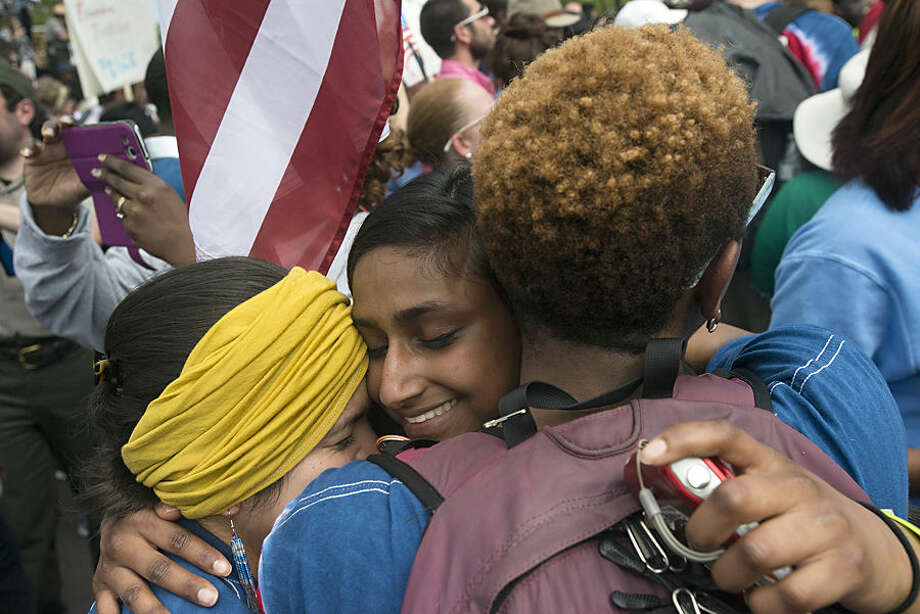 Rani Jacobson, center, embraces Sophie Sarcar, left, and Dominique Skinner after they arrived at the Alabama Capitol while participating in a commemorative march of the 1965 Selma to Montgomery March as part of the National Parks Service 50th Anniversary Walking Classroom outside of Montgomery, Ala., on Wednesday, March 25, 2015. The girls walked most of the distance from Selma to Montgomery over the course of the past five days. (AP Photo/The Montgomery Advertiser, Albert Cesare) NO SALES