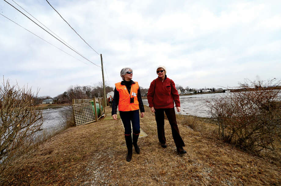 Hour photo / Erik Trautmann Land Trust president Cathy Siever and Mary Verel hike to view Old Trolly peninsula at 2 Nearwater Lane as the Norwalk Land Trust hosts a tour of all of its properties Saturday morning.