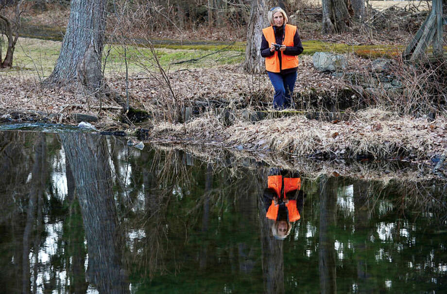 Hour photo / Erik Trautmann Laure Dunne hunts for a photograph at the White Barn Easement at 440 Newtown Ave. as the Norwalk Land Trust hosts a tour of all of its properties Saturday morning.