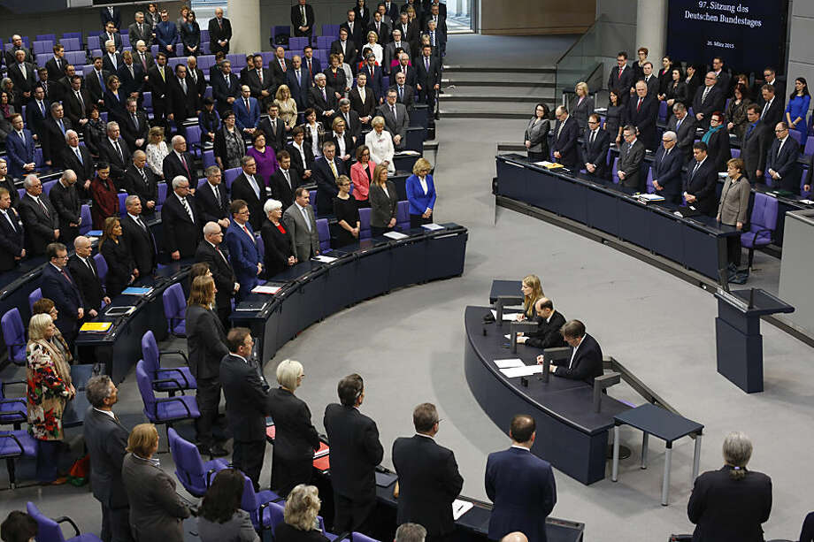 Members of German lawmakers with Chancellor Angela Merkel, right side first row right, hold a minute of silence to commemorate the victims who died in the Germanwings plane crash in the French alps at the parliament Bundestag in Berlin, Germany, Thursday, March 26, 2015. (AP Photo/Markus Schreiber)