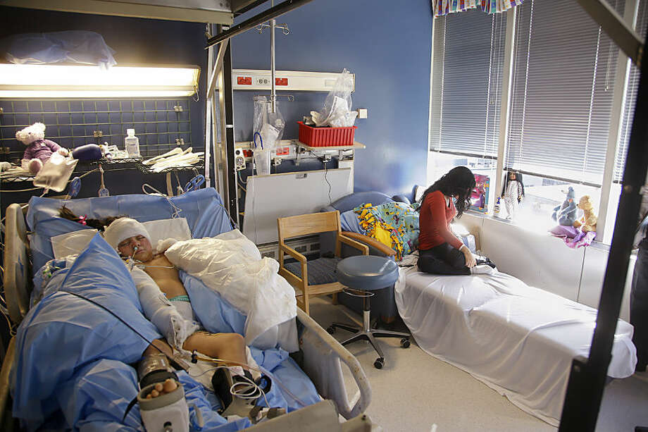 In this Wednesday, March 11, 2015 photo Paola Porter Avila sits on the daybed in her daughter, Paola Matute Porter's, hospital room at the acute care burn unit of the Shriners Hospitals for Children in Boston. Paola Matute was one of more than 70 people injured when a food truck's gas cylinder exploded in a crowded Honduran marketplace Feb. 20, 2015. (AP Photo/Stephan Savoia)