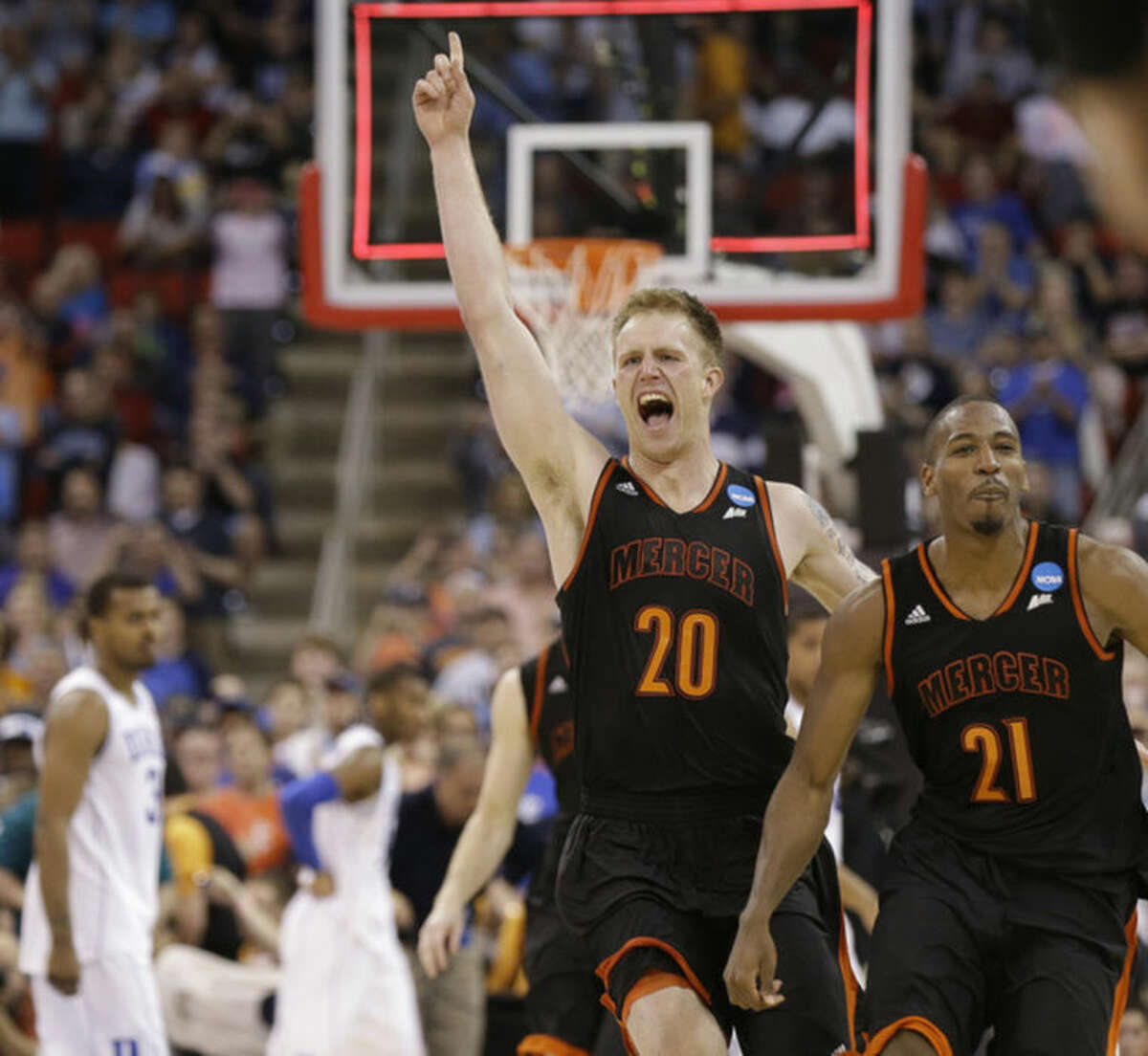 Mercer forward Jakob Gollon (20) and Mercer guard Langston Hall (21) celebrate after the second half of an NCAA college basketball second-round game against Duke, Friday, March 21, 2014, in Raleigh, N.C. Mercer won 78-71. (AP Photo/Gerry Broome)