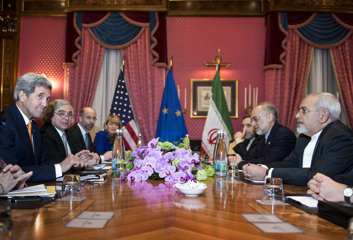 U.S. Secretary of State John Kerry, left, U.S. Secretary of Energy Ernest Moniz, second left, National Security Council point person on the Middle East Robert Malley, 3rd left, and European Union Political Director Helga Schmid. 4th left, head of the Iranian Atomic Energy Organisation Ali Akbar Salehi 2nd right, and Iranian Foreign Minister Mohammad Javad Zarif right wait for the start of a meeting at a hotel in Lausanne Switzerland on Thursday March 26, 2015 during negotiations on the Iranian nuclear programme. (AP Photo/Brendan Smialowski, Pool)
