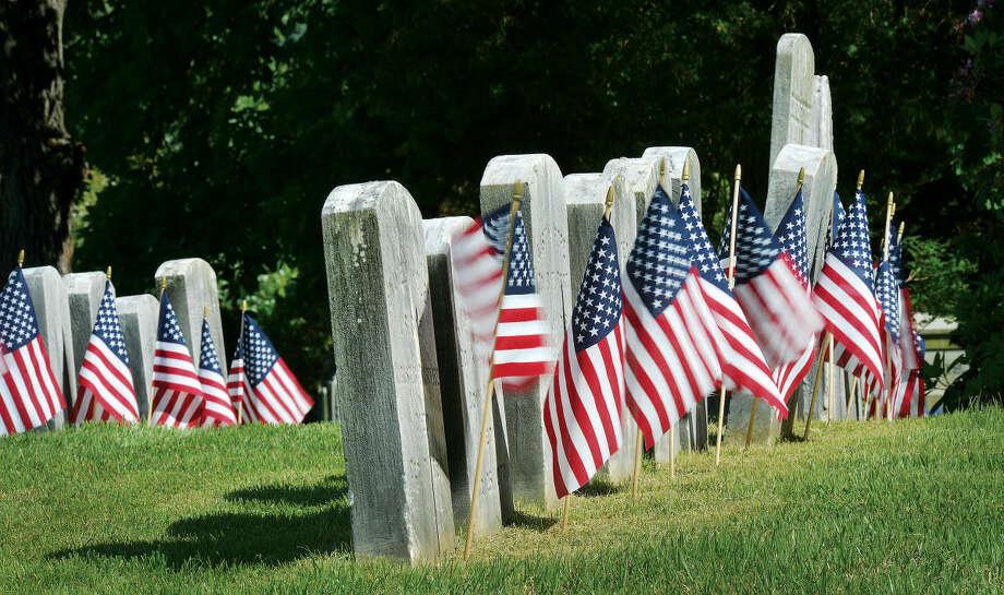 Hour File Photo/Alex von Kleydorff . Under bright skies, flags wave in the wind in front of rows of veterans headstones in Riverside Cemetery