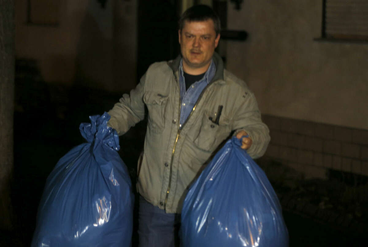 An investigator carries bags with items that have been collected in the house of the family of Andreas Lubitz in Montabaur, Germany, Thursday, March 26, 2015. Lubitz was the copilot on flight Germanwings 9525 that crashed with 150 people on board on Tuesday in the French Alps. (AP Photo/Michael Probst)