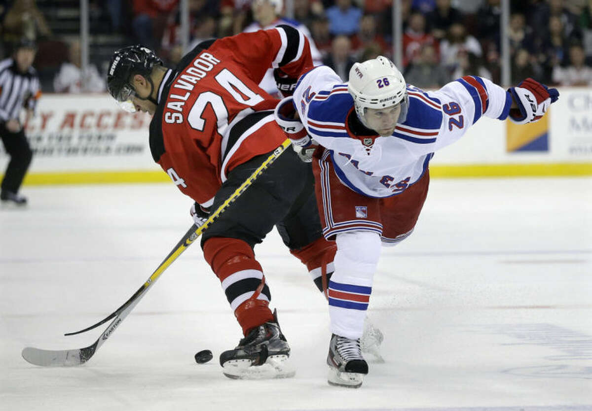 New Jersey Devils' Bryce Salvador (24) gets tied up with New York Rangers' Martin St. Louis (26) during the first period of an NHL hockey game game Saturday, March 22, 2014, in Newark, N.J. (AP Photo/Mel Evans)