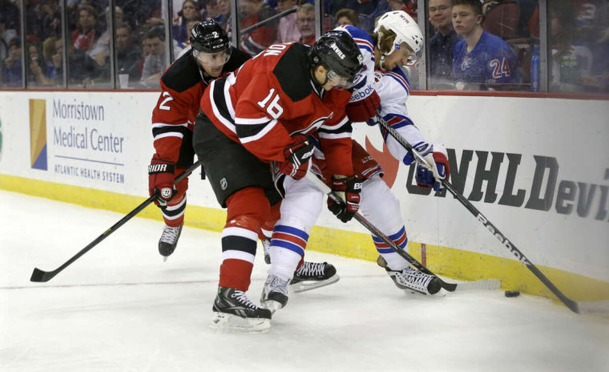 New York Rangers' Carl Hagelin, of Sweden, tries to control the puck as New Jersey Devils' Jacob Josefson (16), of Sweden, and Marek Zidlicky, of the Czech Republic, try to make a steal during the first period of an NHL hockey game game Saturday, March 22, 2014, in Newark, N.J. (AP Photo/Mel Evans)