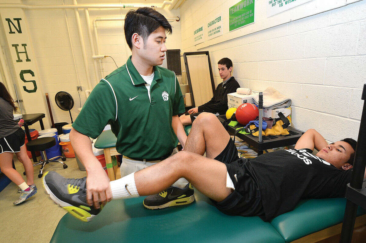 Norwalk athletic trainer Masayoshi Shoji works with a soccer player. (Hour photo/Alex von Kleydorff)