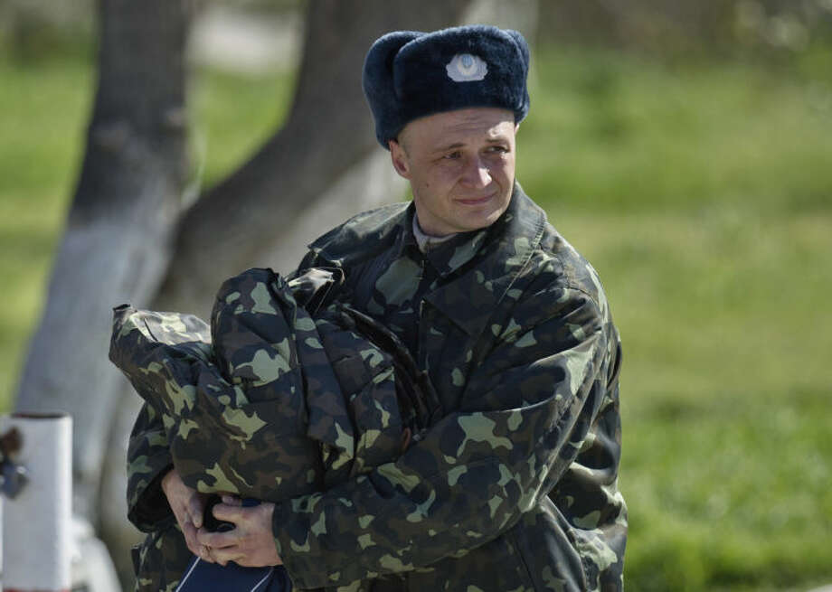 A Ukrainian airman carries belongings as he leaves the Belbek air base, outside Sevastopol, Crimea, Friday, March 21, 2014. The base commander Col. Yuliy Mamchur said he was asked by the Russian military to turn over the base but is unwilling to do so until he receives orders from the Ukrainian defense ministry.(AP Photo/Vadim Ghirda)
