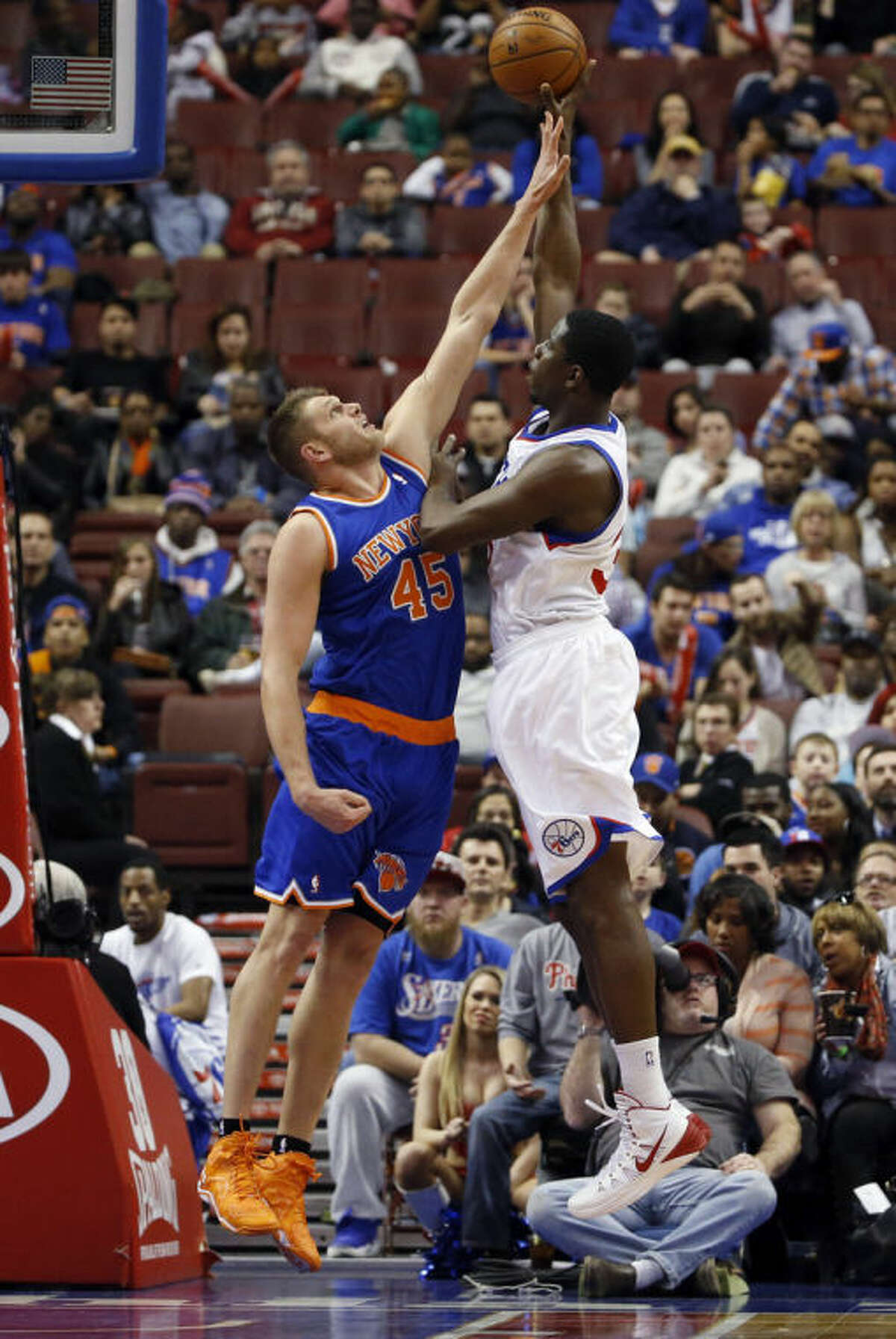 Philadelphia 76ers' Henry Sims, right, goes up for a shot against New York Knicks' Cole Aldrich during the first half of an NBA basketball game, Friday, March 21, 2014, in Philadelphia. (AP Photo/Matt Slocum)
