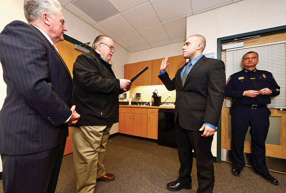 Hour photo / Erik Trautmann Norwalk mayor Harry Rilling looks on as Police Commissioner Charlie Yost swears in three new police officers including Jake Colletto at Norwalk Police Department Headquarters Friday morning.