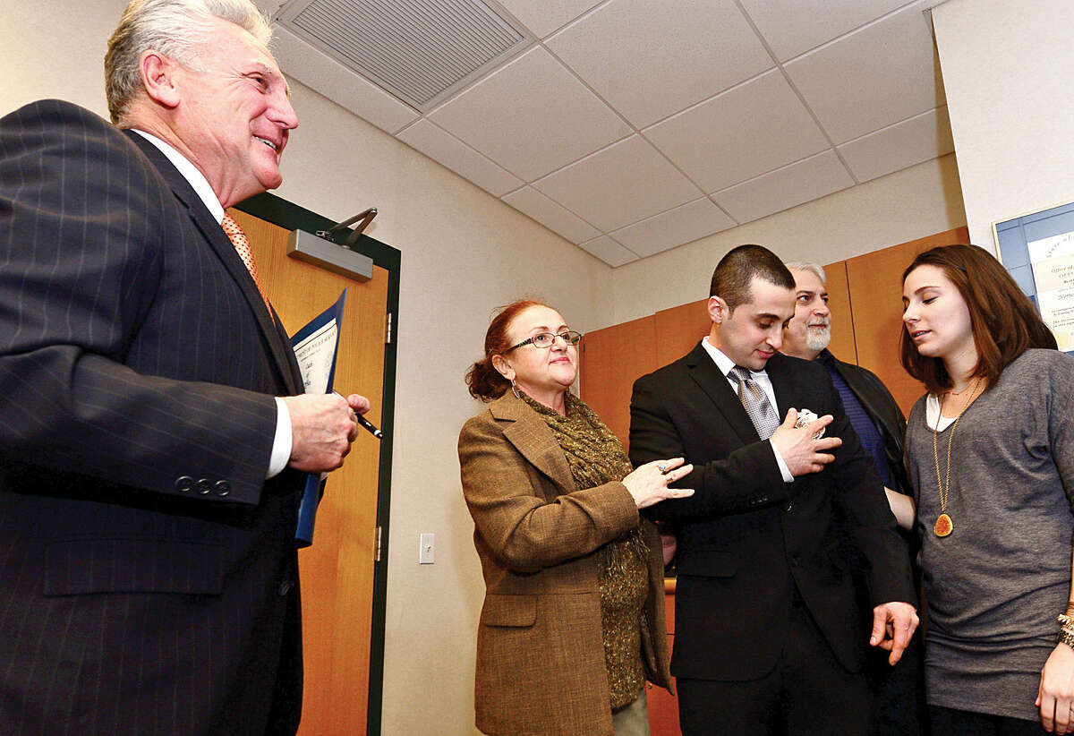 Hour photo / Erik Trautmann New Norwalk police officer Konstantine Arvanitakis is congratulated by family members after being sworn in at Norwalk Police Department Headquarters Friday morning.