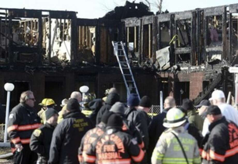 AP photo / David GardAbove, an early morning fire killed four people at the Jersey shore motel whose residents included Superstorm Sandy victims who were staying there because their homes remain uninhabitable nearly a year and a half after the storm, officials said. Three other people were critically injured in the blaze. Below, firefighters investigate an early morning fire at the Mariner's Cove Hotel in Point Pleasant Beach, N.J. on Friday.
