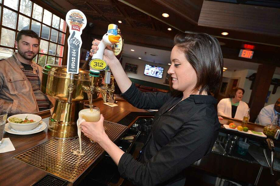 Hour Photo/Alex von Kleydorff Bartender Lianne Carpenter pours a cold beer at Bogey's Grille and Tap Room new location at Wilton Ave and Cross St. in Norwalk