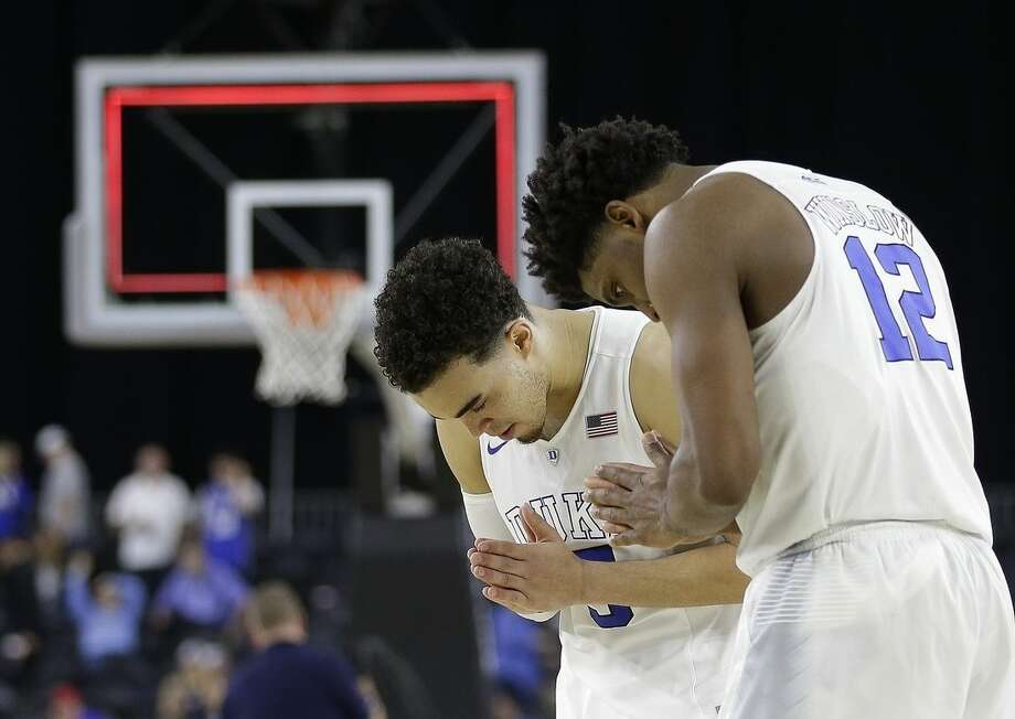 Duke's Justise Winslow (12) and Tyus Jones (5) react after a college basketball regional semifinal game against Utah in the NCAA Tournament Friday, March 27, 2015, in Houston. Duke won 63-57. (AP Photo/David J. Phillip)