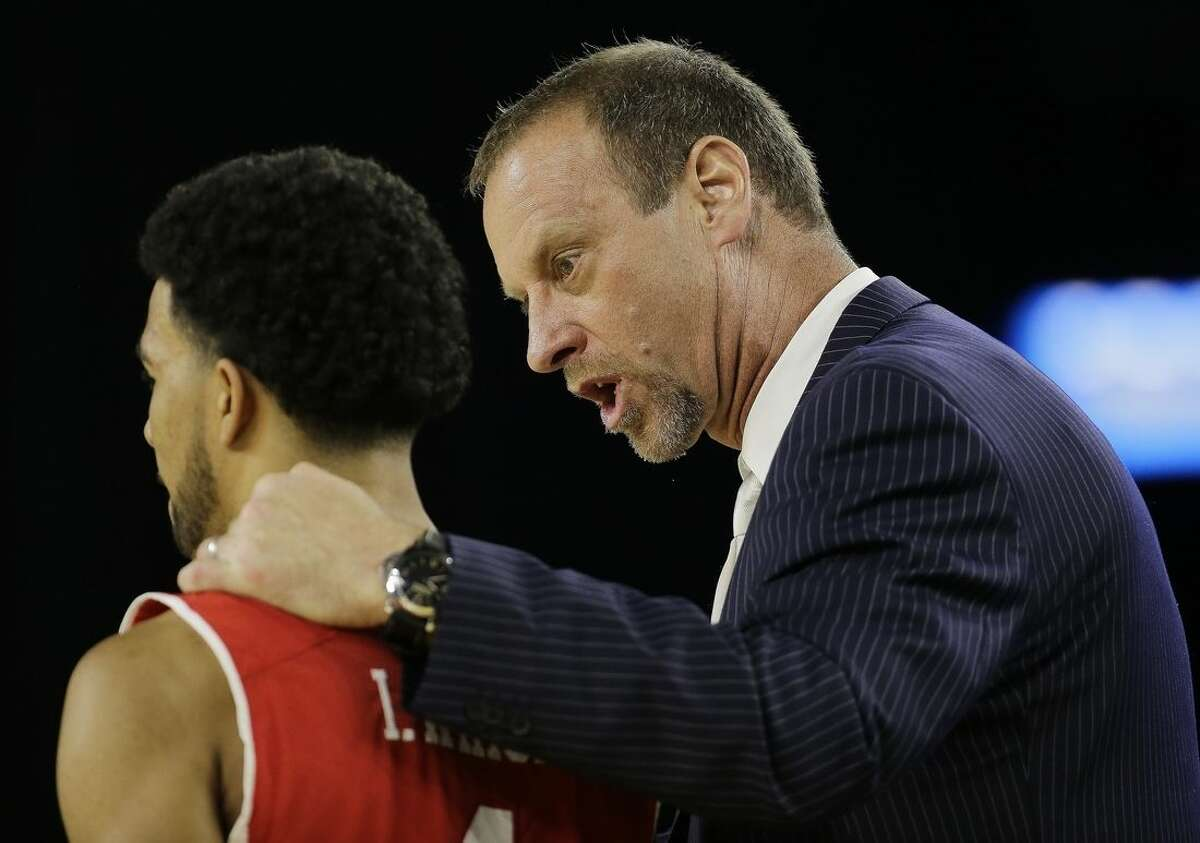Utah head coach Larry Krystkowiak talks to Isaiah Wright during the first half of a college basketball regional semifinal game against Duke in the NCAA Tournament Friday, March 27, 2015, in Houston. (AP Photo/David J. Phillip)