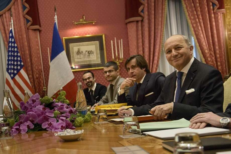 French Foreign Minister Laurent Fabius, right, smiles before the start of a meeting at the Beau Rivage Palace Hotel, in Lausanne, Switzerland, Saturday March 28, 2015. Negotiations over Iran's nuclear program picked up pace on Saturday with the foreign ministers of France and Germany joining U.S. Secretary of State John Kerry in talks with Iran's top diplomat ahead of a looming end-of-March deadline for a preliminary deal. (AP Photo/Brendan Smialowski, Pool)