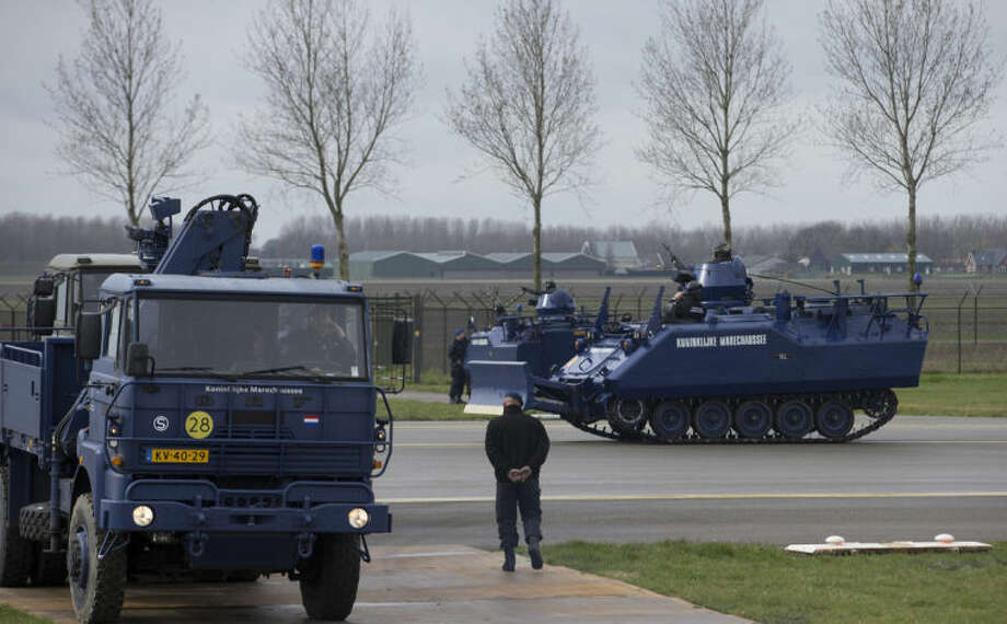 Dutch military police vehicles guard a section of Schiphol airport where China's President Xi Jinping is expected to arrive in Amsterdam, Netherlands, Saturday March 22, 2014. Xi is on a two-day state visit ahead of the March 24 and 25 Nuclear Security Summit in The Hague. (AP Photo/Peter Dejong, Pool)