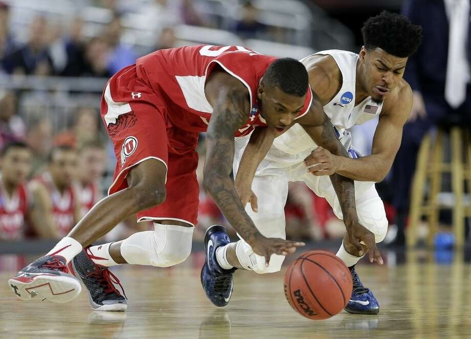 Utah's Delon Wright and Duke's Quinn Cook go after a loose ball during the second half of a college basketball regional semifinal game in the NCAA Tournament Friday, March 27, 2015, in Houston. (AP Photo/Charlie Riedel)