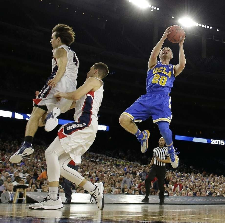 UCLA's Bryce Alford (20) shoots past Gonzaga's Kevin Pangos (4) and Kyle Dranginis during the second half of a college basketball regional semifinal game in the NCAA Tournament Friday, March 27, 2015, in Houston. (AP Photo/Charlie Riedel)