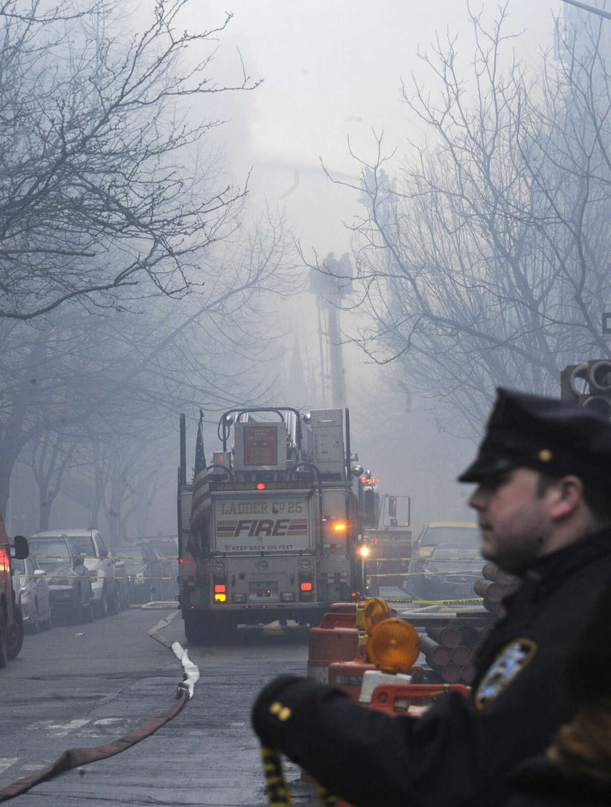 New York City firefighters arrive at the scene of a large fire and a partial building collapse in the East Village neighborhood of New York on Thursday, March 26, 2015. Orange flames and black smoke are billowing from the facade and roof of the building near several New York University buildings. (AP Photo/ Louis Lanzano)
