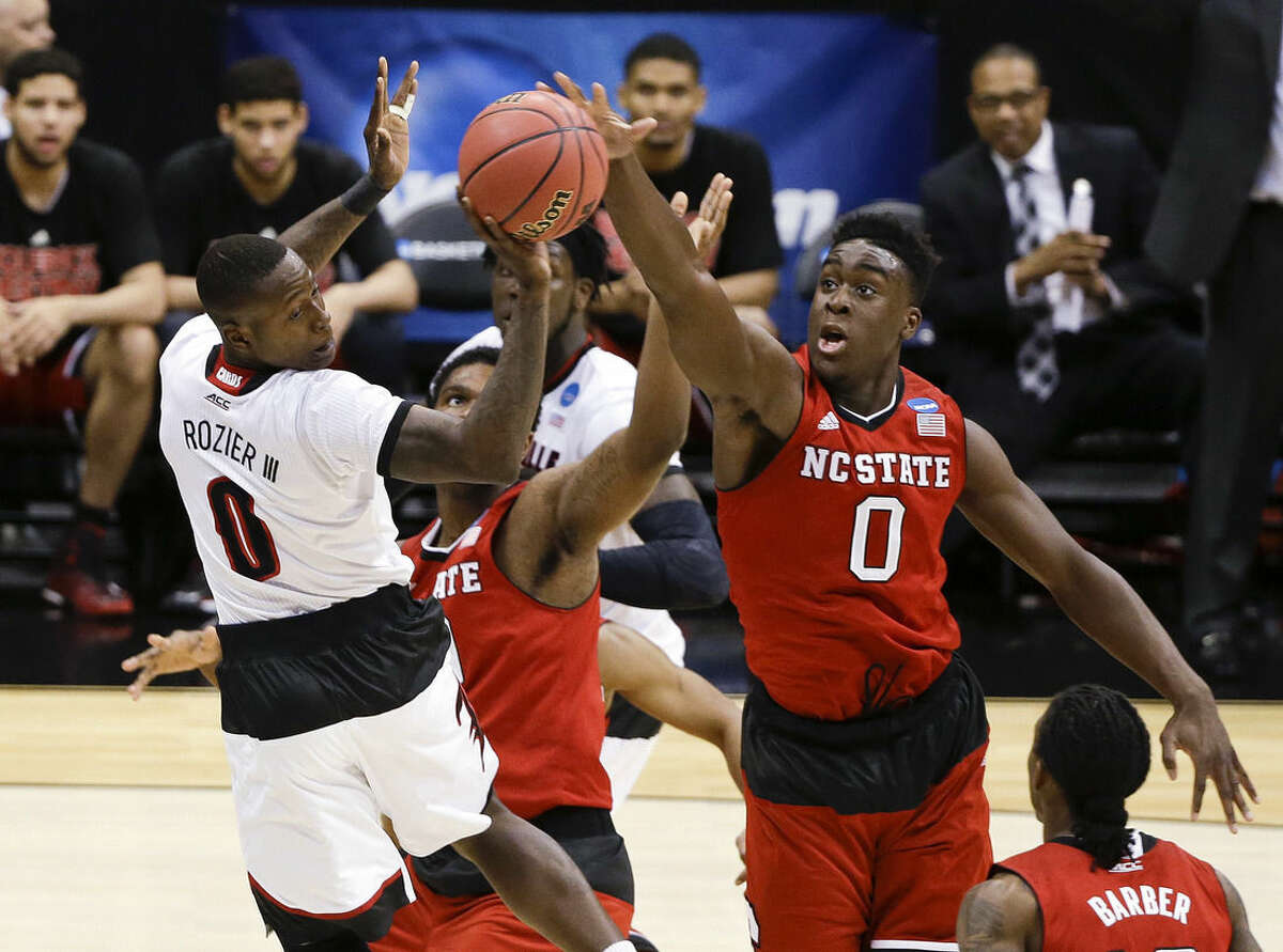 Louisville's Terry Rozier (0) passes away from North Carolina State's Abdul-Malik Abu (0) during the first half of a regional semifinal in the NCAA men's college basketball tournament Friday, March 27, 2015, in Syracuse, N.Y. (AP Photo/Seth Wenig)