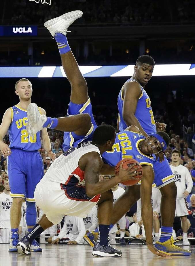 UCLA's Kevon Looney (5) falls over Gonzaga's Gary Bell Jr. during the second half of a college basketball regional semifinal game in the NCAA Tournament Friday, March 27, 2015, in Houston. (AP Photo/David J. Phillip)