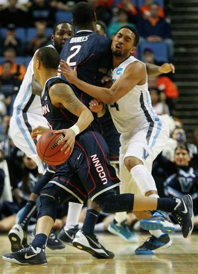 Villanova's Darrun Hilliard II (4) runs into a pick set by Connecticut's DeAndre Daniels (2) as he chases Shabazz Napier during the first half of a third-round game in the NCAA men's college basketball tournament in Buffalo, N.Y., Saturday, March 22, 2014. (AP Photo/Bill Wippert) / FR170745 AP