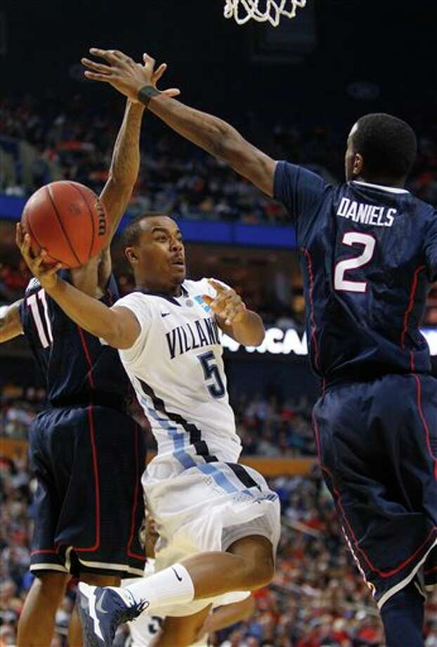 Villanova's Tony Chennault (5) passes between Connecticut's Ryan Boatright (11) and DeAndre Daniels (2) during the first half of a third-round game in the NCAA men's college basketball tournament in Buffalo, N.Y., Saturday, March 22, 2014. (AP Photo/Bill Wippert) / FR170745 AP