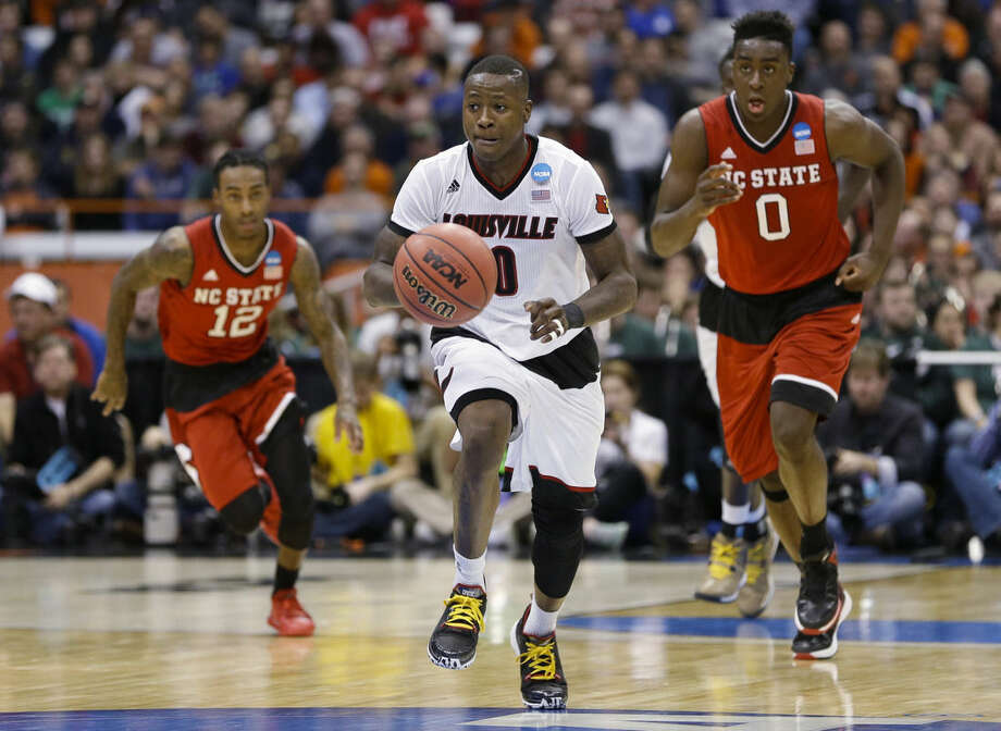 Louisville's Terry Rozier (0) breaks away from North Carolina State's Abdul-Malik Abu (0) and Anthony Barber (12) during the first half of a regional semifinal in the NCAA men's college basketball tournament Friday, March 27, 2015, in Syracuse, N.Y. (AP Photo/Seth Wenig)