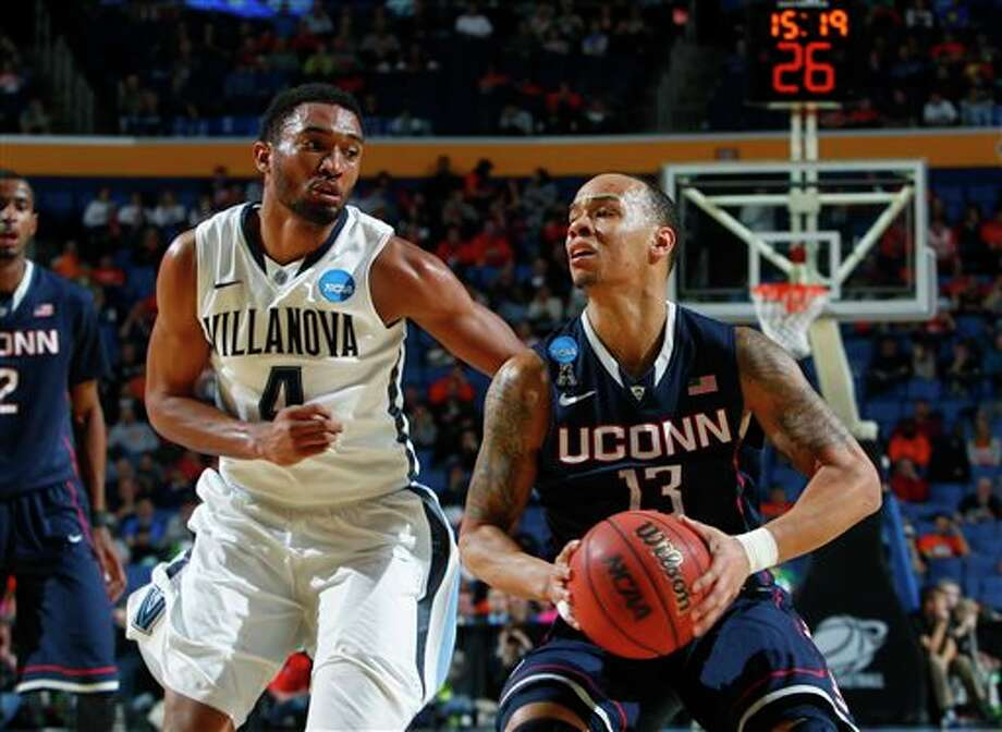 Villanova's Darrun Hilliard II (4) defends Connecticut's Shabazz Napier (13) during the second half of a third-round game in the NCAA men's college basketball tournament in Buffalo, N.Y., Saturday, March 22, 2014. (AP Photo/Bill Wippert) / FR170745 AP