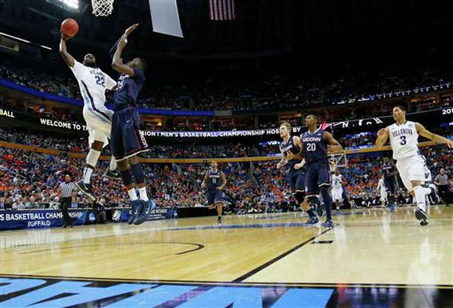 Villanova's JayVaughn Pinkston (22) shoots over Connecticut's Amida Brimah (35) during the first half of a third-round game in the NCAA men's college basketball tournament in Buffalo, N.Y., Saturday, March 22, 2014. (AP Photo/Bill Wippert) / FR170745 AP