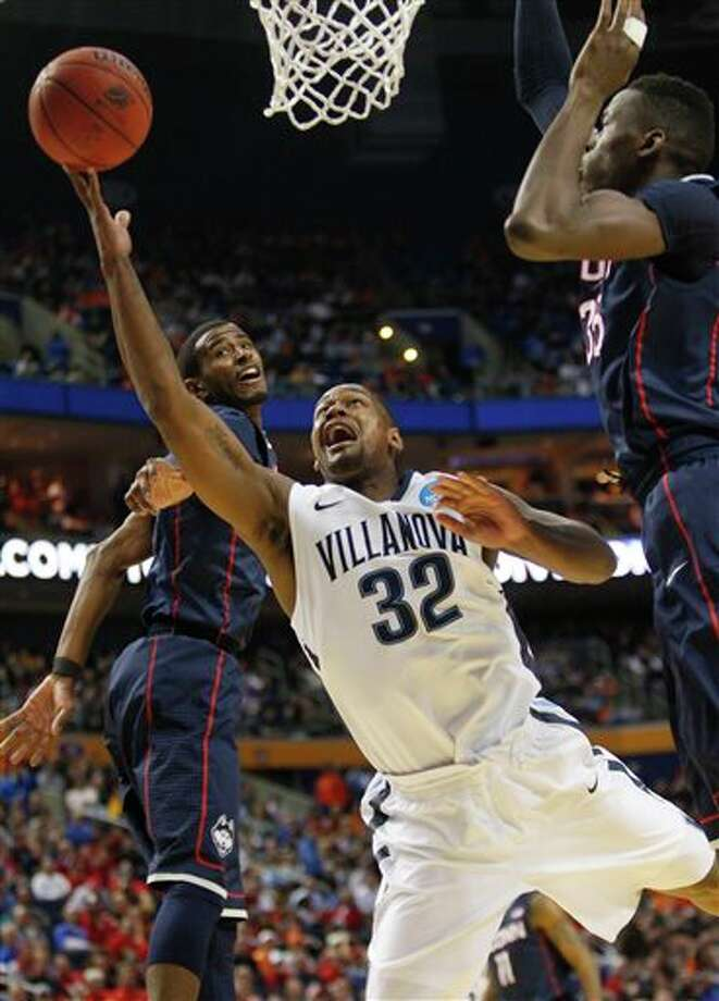 Villanova's James Bell (32) drives past Connecticut's Amida Brimah (35) during the first half of a third-round game in the NCAA men's college basketball tournament in Buffalo, N.Y., Saturday, March 22, 2014. (AP Photo/Bill Wippert) / FR170745 AP