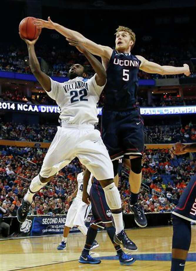 Villanova's JayVaughn Pinkston (22) drives past Connecticut's Niels Giffey (5) during the first half of a third-round game in the NCAA men's college basketball tournament in Buffalo, N.Y., Saturday, March 22, 2014. (AP Photo/Bill Wippert) / FR170745 AP