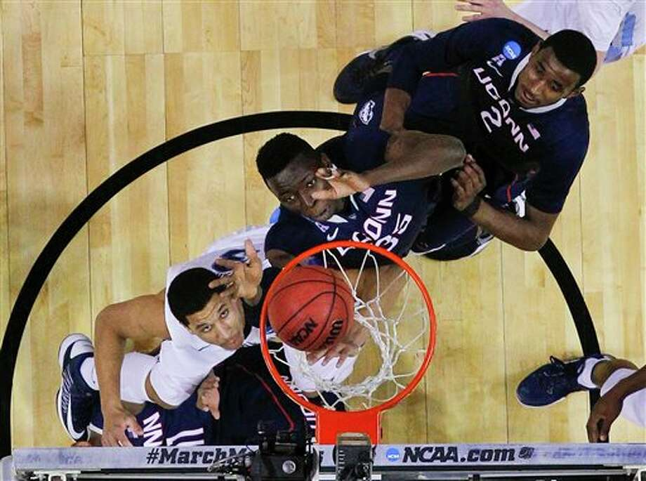Connecticut's Amida Brimah (35) and Connecticut's DeAndre Daniels (2) and Villanova's Josh Hart look for a rebound during the first half of a third-round game in the NCAA men's college basketball tournament in Buffalo, N.Y., Saturday, March 22, 2014. (AP Photo/Bill Wippert) / FR170745 AP