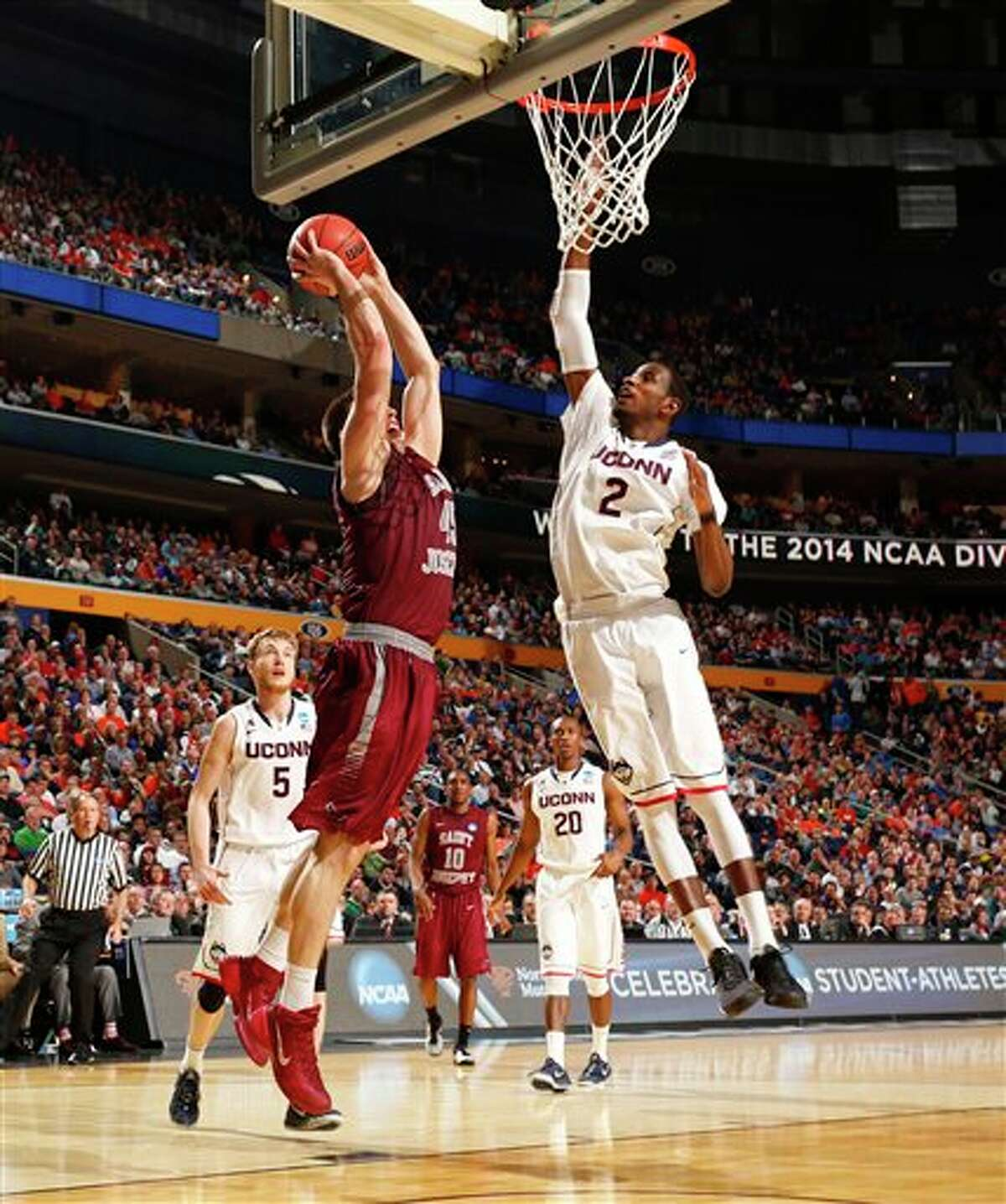 Saint Joseph's forward Halil Kanacevic (45) dunks against Connecticut forward DeAndre Daniels (2) during the second half of a second-round game in the NCAA college basketball tournament in Buffalo, N.Y., Thursday, March 20, 2014. (AP Photo/Bill Wippert)