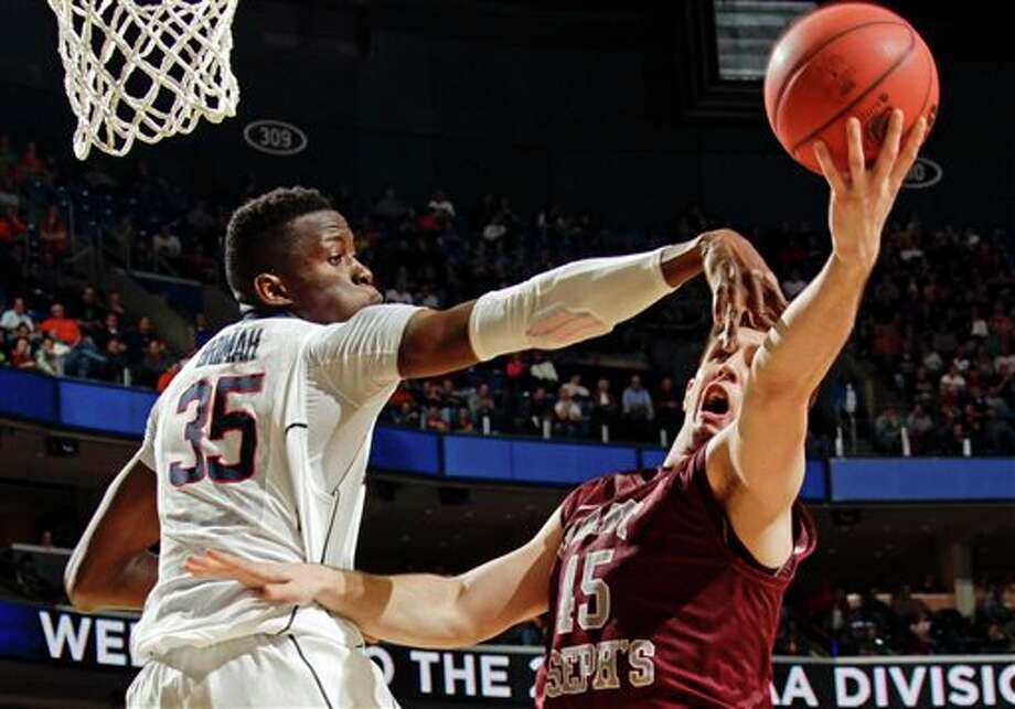 Saint Joseph's Halil Kanacevic (45) shoots over Connecticut's Amida Brimah (35) during the second half of a second-round game in the NCAA college basketball tournament in Buffalo, N.Y., Thursday, March 20, 2014. (AP Photo/Bill Wippert) / FR170745 AP