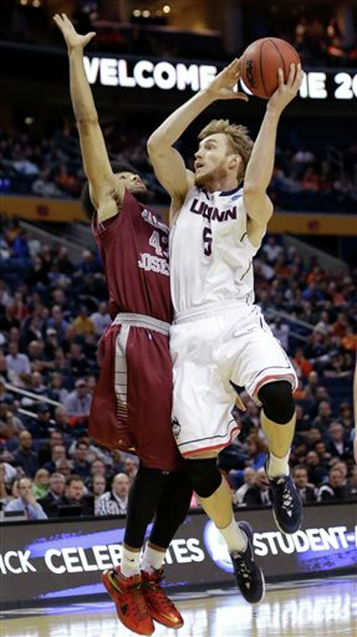 Connecticut's Niels Giffey (5) shoots over Saint Joseph's DeAndre Bembry (43) during the first half of a second-round game in the NCAA men's college basketball tournament in Buffalo, N.Y., Thursday, March 20, 2014. (AP Photo/Frank Franklin II)