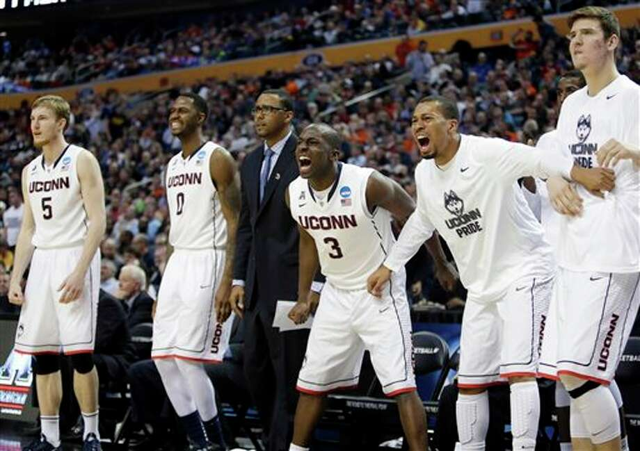 Connecticut's Terrence Samuel (3) joins teammates Niels Giffey (5) and Phillip Nolan (0) as he cheers during overtime of a second-round game against Saint Joseph's in the NCAA college basketball tournament in Buffalo, N.Y., Thursday, March 20, 2014. Connecticut won 89-81. (AP Photo/Nick LoVerde) / FR1171125 AP