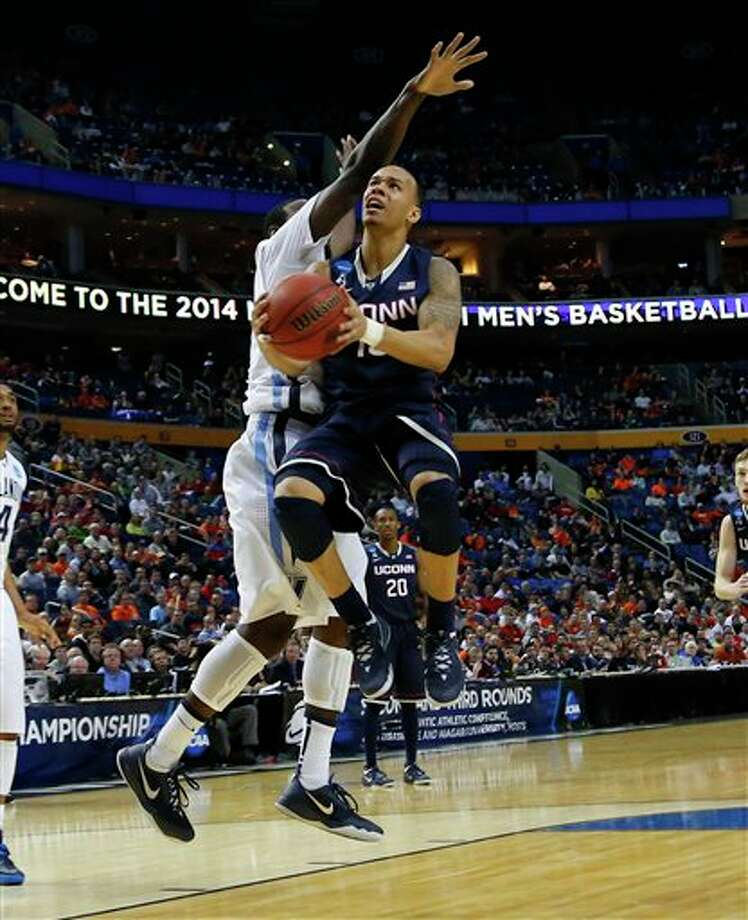 Connecticut guard Shabazz Napier (13) drive to the basket against Villanova forward JayVaughn Pinkston during the second half of a third-round game in the NCAA men's college basketball tournament in Buffalo, N.Y., Saturday, March 22, 2014. Connecticut defeated Villanova, 77-65. (AP Photo/Bill Wippert) / FR170745 AP