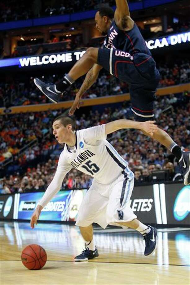 Villanova's Ryan Arcidiacono (15) drives under Connecticut's Ryan Boatright during the first half of a third-round game in the NCAA men's college basketball tournament in Buffalo, N.Y., Saturday, March 22, 2014. (AP Photo/Bill Wippert) / FR170745 AP