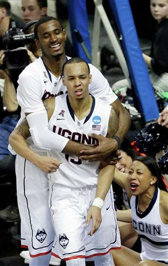 Connecticut's DeAndre Daniels hugs Shabazz Napier, front, after Napier scored after a foul during overtime of a second-round game against Saint Joseph's in the NCAA college basketball tournament in Buffalo, N.Y., Thursday, March 20, 2014. Connecticut won 89-81. (AP Photo/Frank Franklin II) / AP