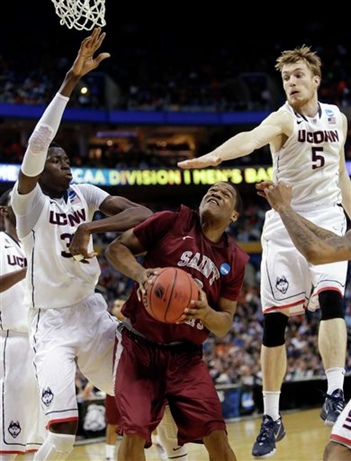 Connecticut's Niels Giffey (5) and Amida Brimah, left, defend Saint Joseph's Ronald Roberts, Jr., center, during the first half of a second-round game in the NCAA college basketball tournament in Buffalo, N.Y., Thursday, March 20, 2014. (AP Photo/Nick LoVerde)