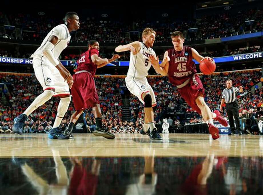 Saint Joseph's 's Halil Kanacevic (45) drives past Connecticut's Niels Giffey (5) during the second half of a second-round game in the NCAA college basketball tournament in Buffalo, N.Y., Thursday, March 20, 2014. (AP Photo/Bill Wippert) / FR170745 AP