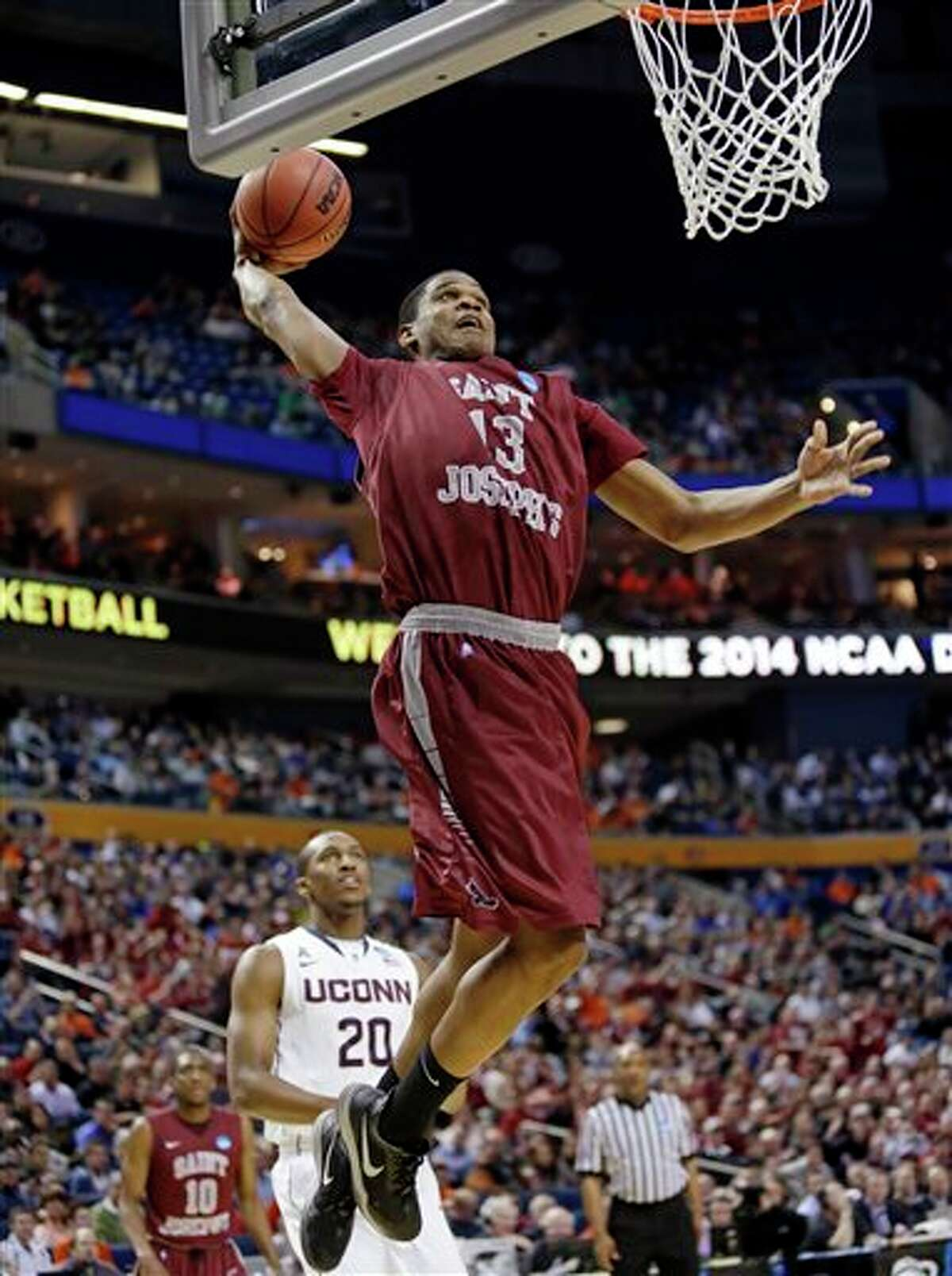 Saint Joseph's Ronald Roberts, Jr. (13) dunks the ball in front of Connecticut's Lasan Kromah (20) during the first half of a second-round game in the NCAA college basketball tournament in Buffalo, N.Y., Thursday, March 20, 2014. (AP Photo/Nick LoVerde)