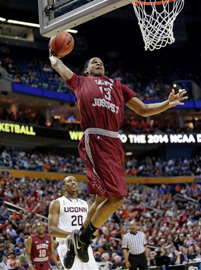 Saint Joseph's Ronald Roberts, Jr. (13) dunks the ball in front of Connecticut's Lasan Kromah (20) during the first half of a second-round game in the NCAA college basketball tournament in Buffalo, N.Y., Thursday, March 20, 2014. (AP Photo/Nick LoVerde) / FR1171125 AP