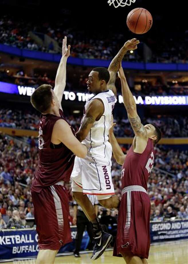 Connecticut's Ryan Boatright, center, passes away from Saint Joseph's Chris Wilson, right, and Halil Kanacevic, left, during the second half of a second-round game in the NCAA college basketball tournament in Buffalo, N.Y., Thursday, March 20, 2014. (AP Photo/Nick LoVerde) / FR1171125 AP