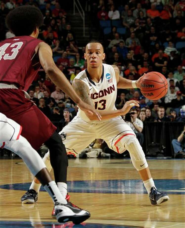Connecticut guard Shabazz Napier (13) drives against Saint Joseph's forward DeAndre Bembry (43) during the first half of a second-round game in the NCAA college basketball tournament in Buffalo, N.Y., Thursday, March 20, 2014. (AP Photo/Bill Wippert) / FR170745 AP